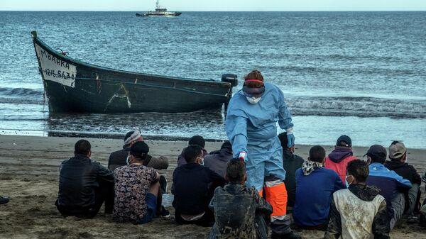 Мигрантам из Марокко проверяют температуру после прибытия на побережье Канарских островов