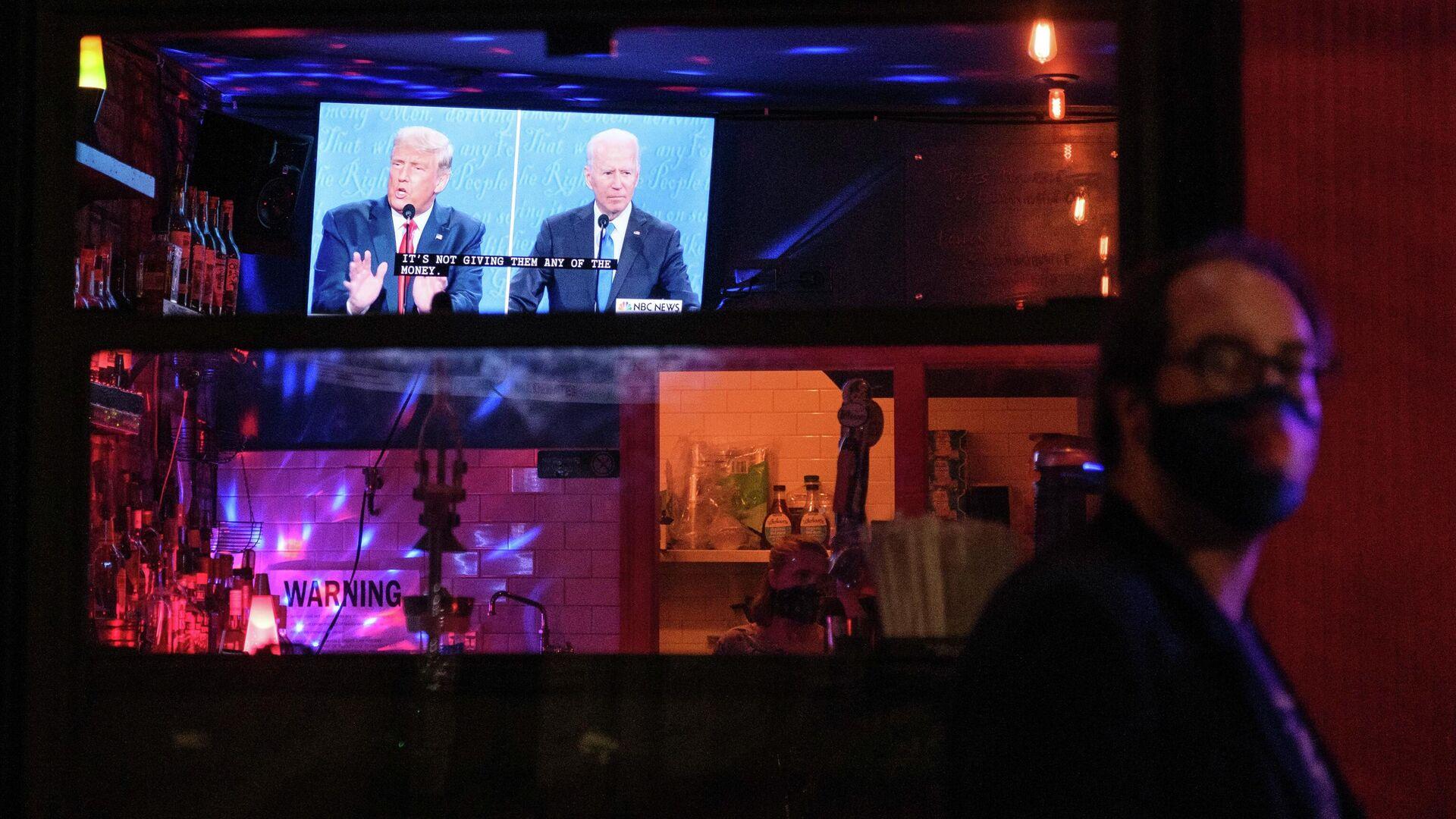 Жители Нью-Йорка смотрят трансляцию финального раунда дебатов с участием президента США Дональда Трампа и его соперника - кандидата в президенты США от Демократической партии Джо Байдена - РИА Новости, 1920, 04.11.2020