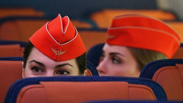 Стюардессы в салоне дальнемагистрального широкофюзеляжного пассажирского самолета Airbus A350-900