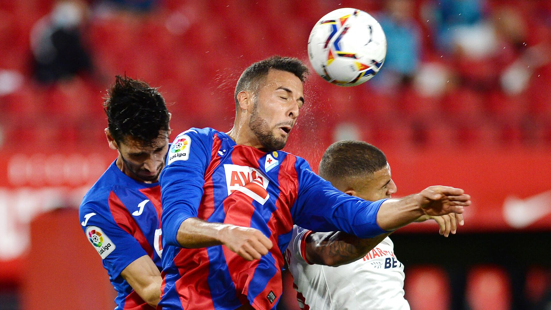 Eibar's Argentinian defender Esteban Burgos (C) jumps for the ball with Eibar's Portuguese defender Paulo Oliveira (L) and Sevilla's Brazilian defender Diego Carlos during the Spanish League football match between Sevilla and Eibar at the Sanchez Pizjuan stadium in Sevilla on October 24, 2020. (Photo by CRISTINA QUICLER / AFP) - РИА Новости, 1920, 24.10.2020