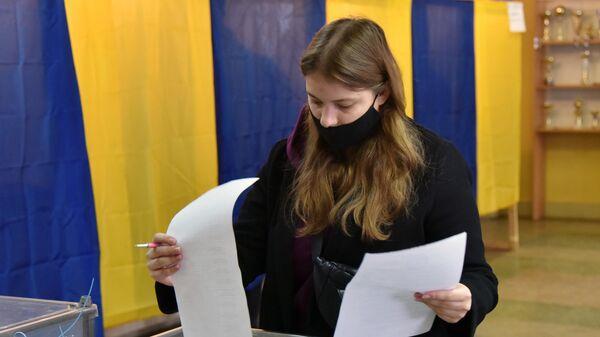 Девушка голосует на одном из избирательных участков во Львове