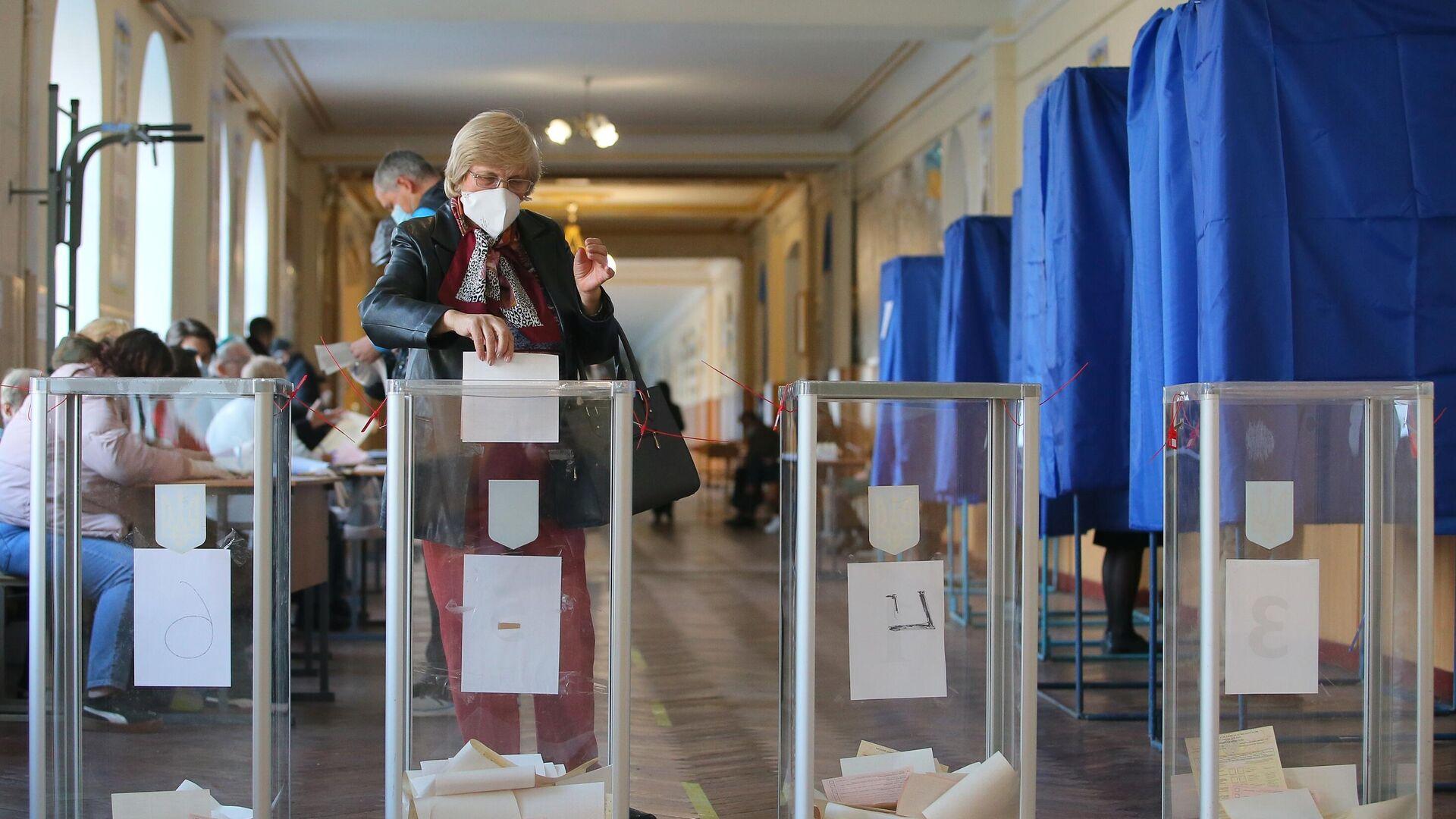 Женщина голосует на одном из избирательных участков в Киеве - РИА Новости, 1920, 31.10.2020