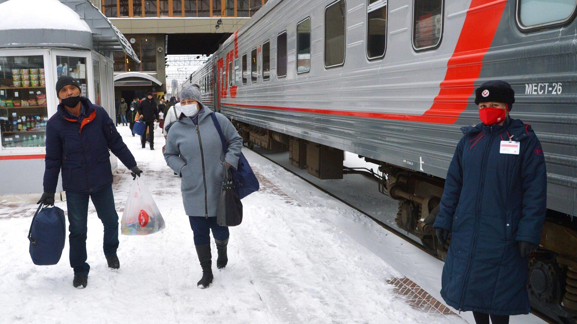 Пассажиры и проводница в защитных масках на перроне железнодорожного вокзала - РИА Новости, 1920, 13.12.2020