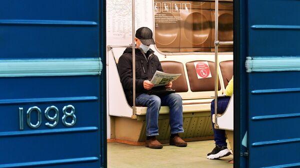 Пассажир в медицинской маске в вагоне поезда на станции метро Марьино Московского метрополитена