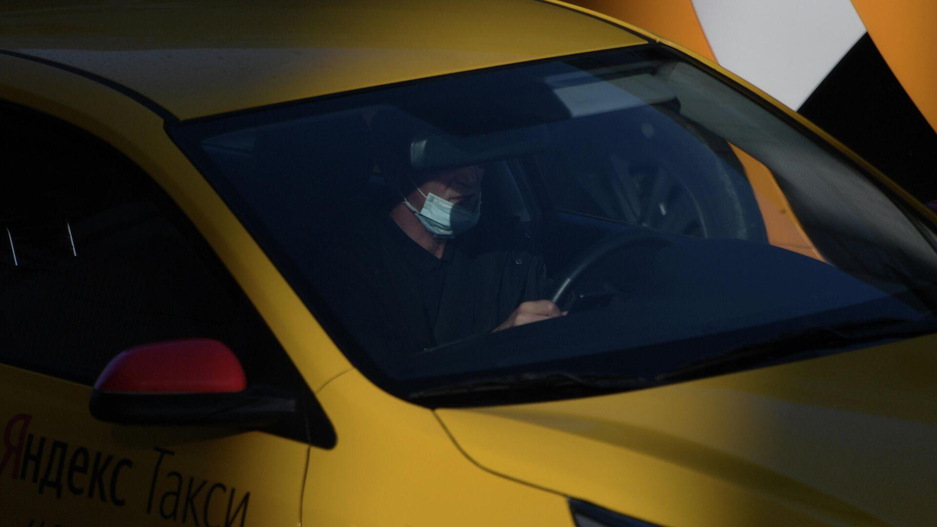 Водитель в защитной маске за рулем такси в Москве - РИА Новости, 1920, 12.09.2021