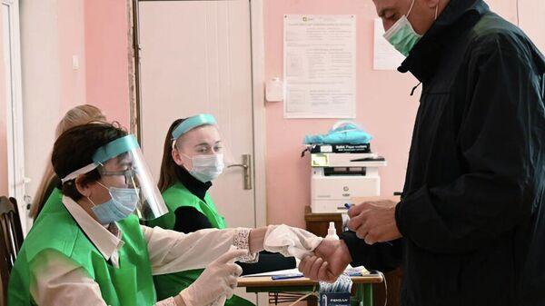 Дезинфекция рук на одном из избирательных участков в Тбилиси, где проходит голосование на парламентских выборах в Грузии