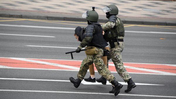 Сотрудники правоохранительных органов задерживают участника несанкционированной акции Дзяды в Минске