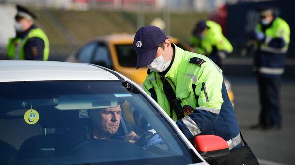 Сотрудник дорожно-патрульной службы ГИБДД выписывает штраф водителю