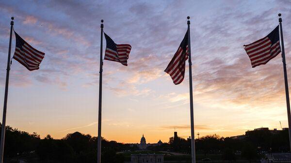 Флаги США около монумента первому президенту США Джорджу Вашингтону в Вашингтоне
