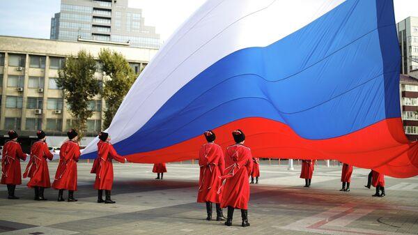 Торжественная церемония поднятия Государственного флага Российской Федерации казаками почётного караула Кубанского казачьего войска в День народного единства на главной городской площади в Краснодаре