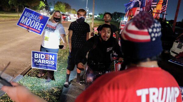 Сторонники Джо Байдена сталкиваются со сторонниками Трампа на избирательном участке в день выборов в Хьюстоне, штат Техас