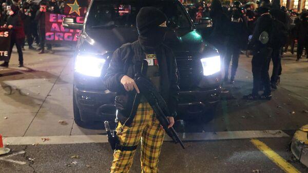 Женщина c оружием во время акции протеста в Портленде, штат Орегон, США. 4 ноября 2020 года