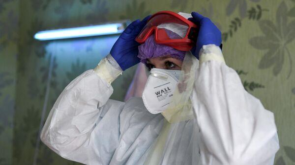 Медицинский работник переодевается в защитный костюм в ковидном госпитале на базе санатория Прибой в Евпатории