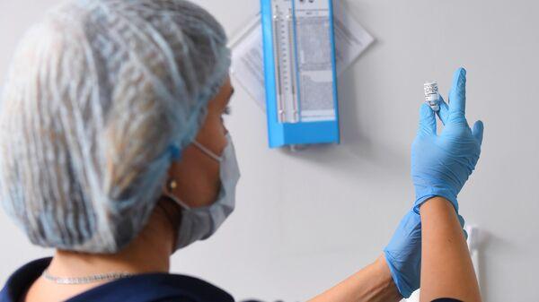 Медицинский работник набирает в шприц вакцину против COVID-19