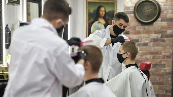 Парикмахер стрижет клиента в одной из парикмахерских Симферополя
