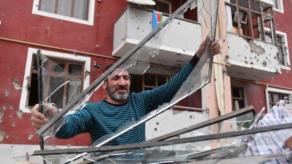 Мужчина выбрасывает стекла, разбитые в результате обстрелов в поселке Шырарх Тертерского района