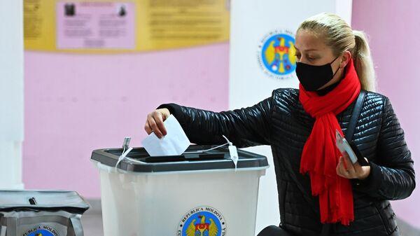 Женщина голосует во время второго тура на выборах президента Молдавии на избирательном участке в Кишиневе