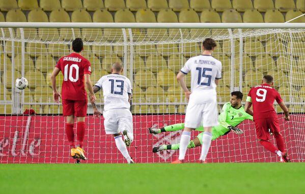 Нападающий сборной Турции Дженк Тосун (справа) реализует пенальти