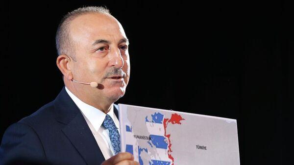 Министр иностранных дел Турции Мевлют Чавушоглу показывает карту Греции и Турции во время выступления на конференции в Братиславе