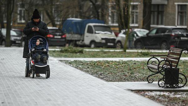 Женщина с коляской идет по обледеневшему тротуару на одной из улиц в Москве