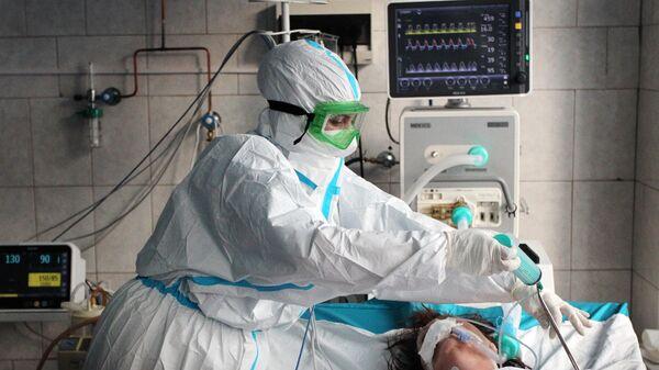 Медицинский работник и пациент в отделении интенсивной терапии ковид-госпиталя в городе Новоалтайске