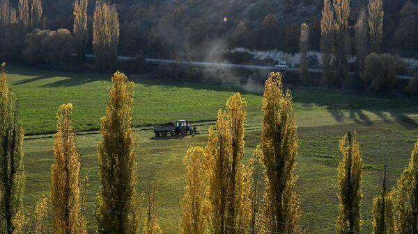 Трактор едет по полю в Бахчисарайском районе Республики Крым