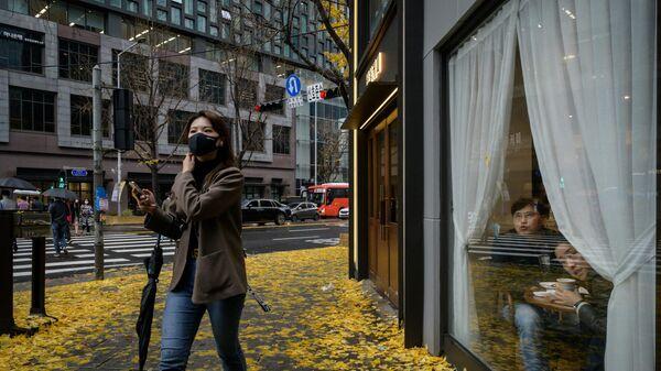 Женщина в маске  на улице в Сеуле, который готовится к третьей волне коронавируса