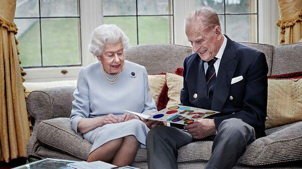 Британская королева Елизавета и принц Филипп, герцог Эдинбургский, с самодельной открыткой, подаренной на годовщину свадьбы их правнуками принцем Джорджем, принцессой Шарлоттой и принцем Луи