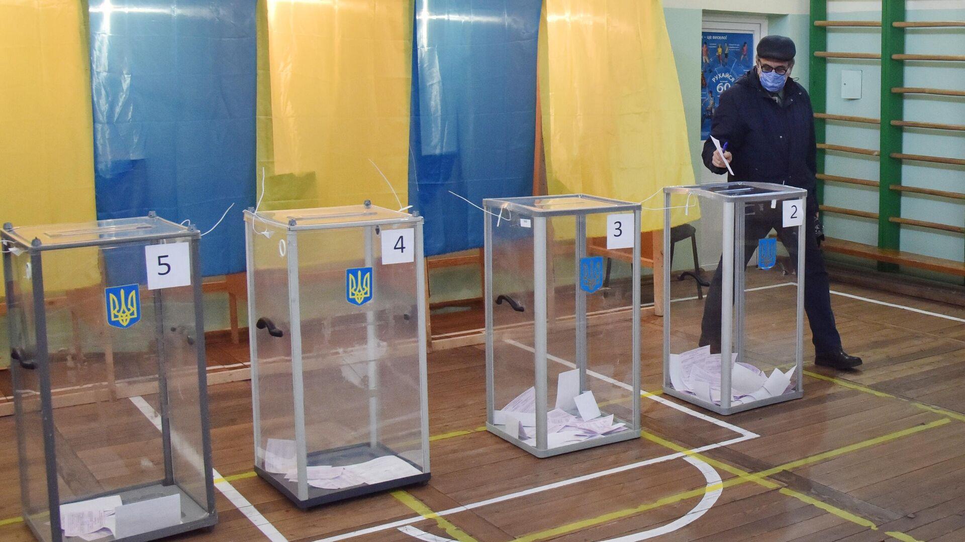 Мужчина голосует на избирательном участке во Львове - РИА Новости, 1920, 28.11.2020