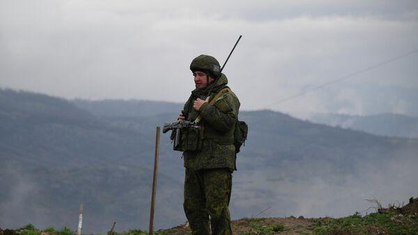 Российский миротворец обеспечивает контроль за безопасностью передвижения автотранспорта на дороге Степанакерт - Шуша