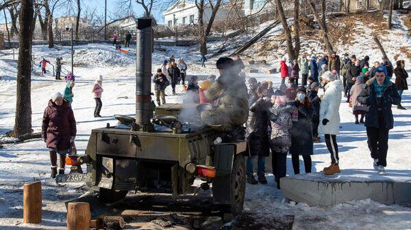 Местные жители стоят в очереди возле полевой кухни во Владивостоке