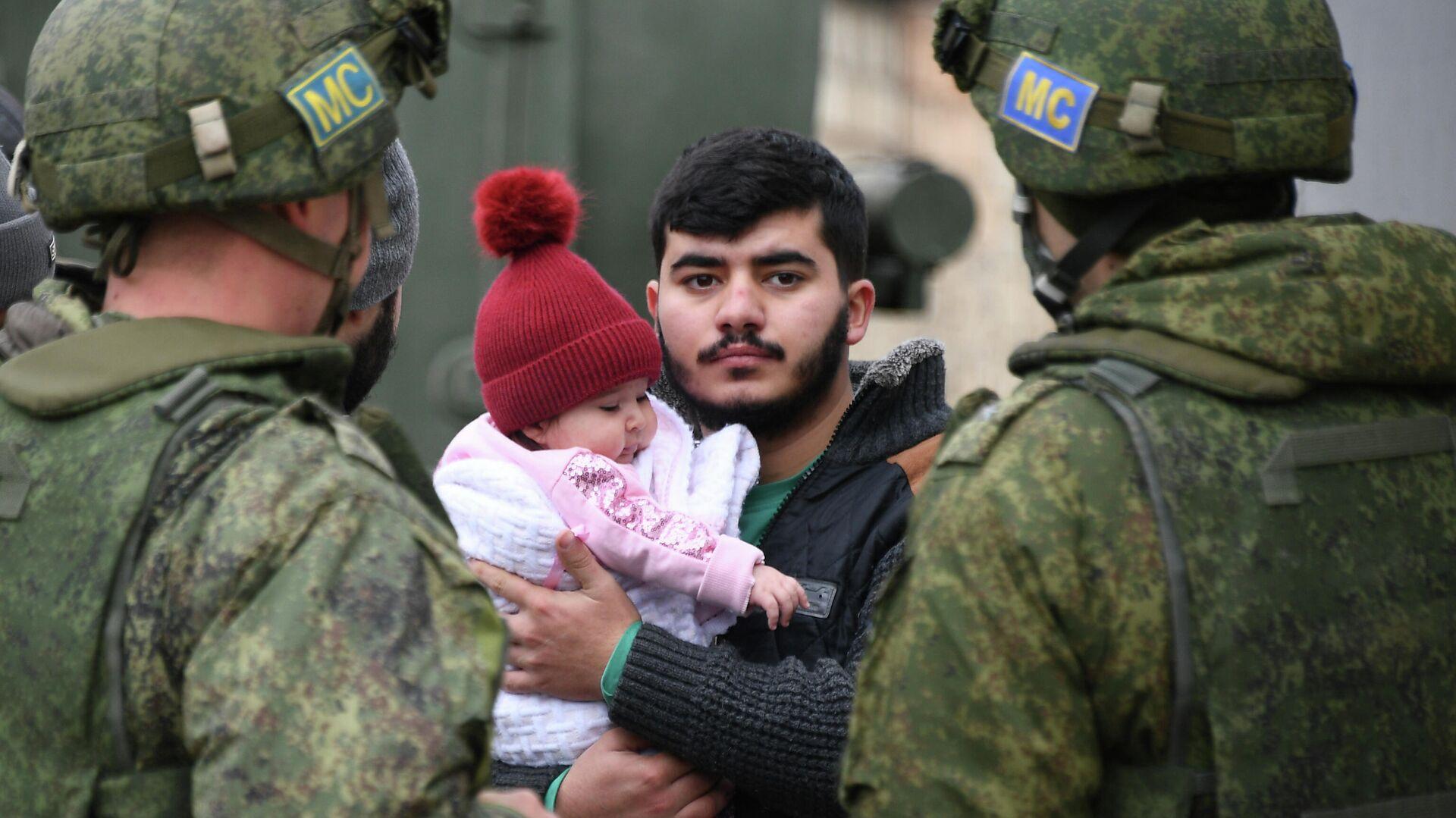 Мужчина с ребенком стоит рядом с российскими миротворцами - РИА Новости, 1920, 24.11.2020