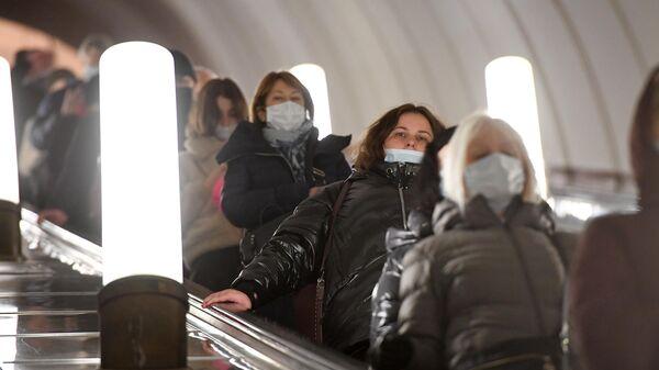 Пассажиры в медицинских масках на эскалаторе Московского метрополитена