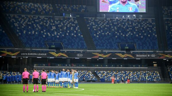 A screen displays a photo of late Argentinian football legend Diego Maradona as players hold a minute of silence in homage to Maradona prior to the UEFA Europe League Group F football match Napoli vs Rijeka on November 26, 2020 at the San Paolo stadium in Naples. - Maradona, widely remembered for his Hand of God goal against England in the 1986 World Cup quarter-finals, died on November 25, 2020 of a heart attack at his home near Buenos Aires in Argentina, while recovering from surgery to remove a blood clot on his brain. (Photo by Filippo MONTEFORTE / AFP)
