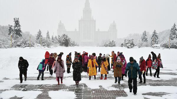 Туристы на Аллее ученых возле смотровой площадки Воробьевых гор во время снегопада