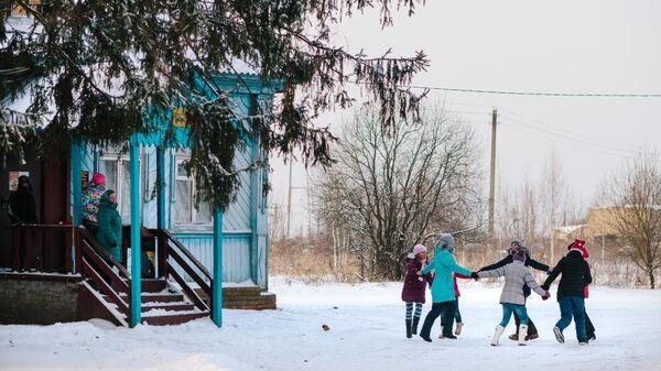 Дети водят хоровод у сельского Дома культуры в Ивановской области