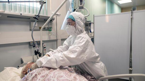 Медицинский работник и пациент в отделении реанимации и интенсивной терапии в госпитале для больных COVID-19 в  Московском клиническом центре инфекционных болезней Вороновское