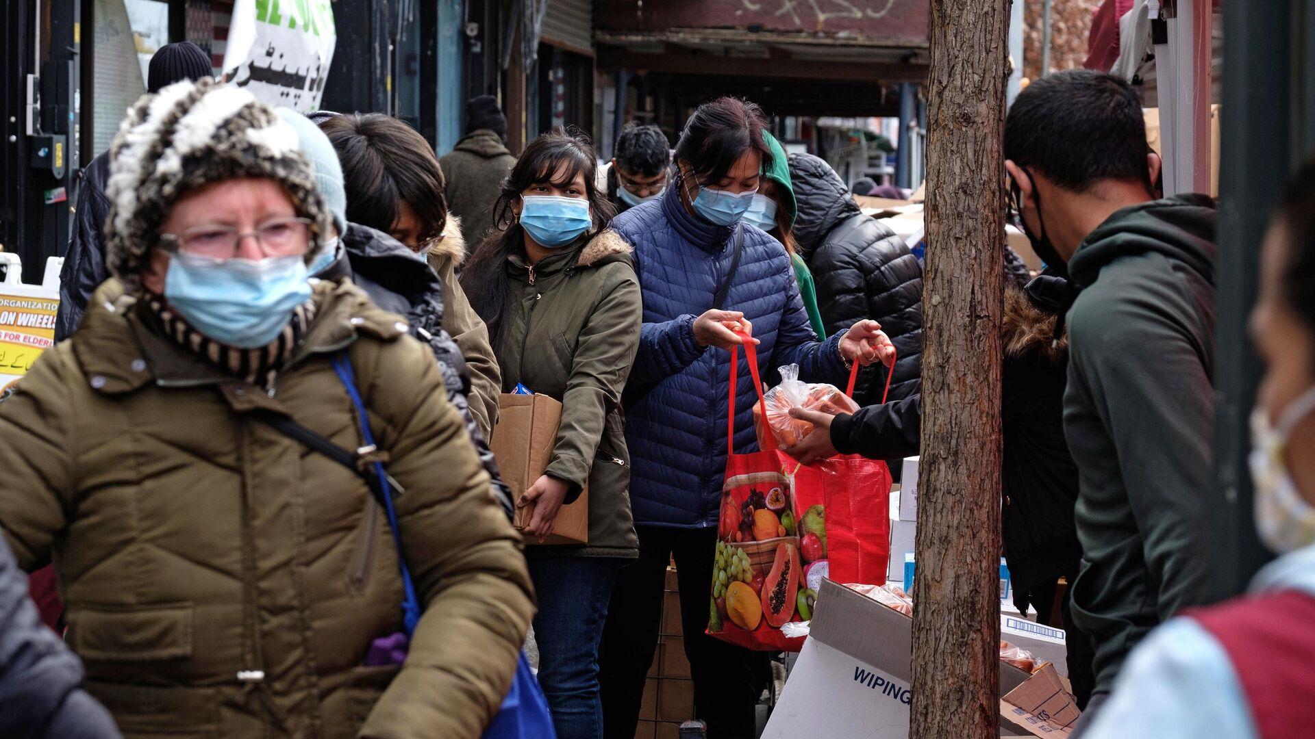 Сотрудник раздает продукты в пункте бесплатной раздачи еды в День благодарения в Бруклине - РИА Новости, 1920, 04.12.2020