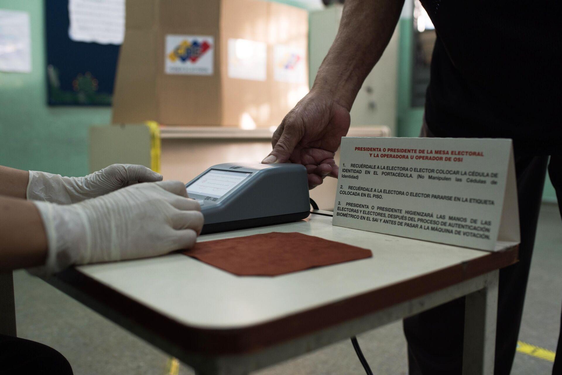 Проверка личности избирателя на избирательном участке во время голосования на выборах в Нацассамблею в Венесуэле - РИА Новости, 1920, 07.12.2020