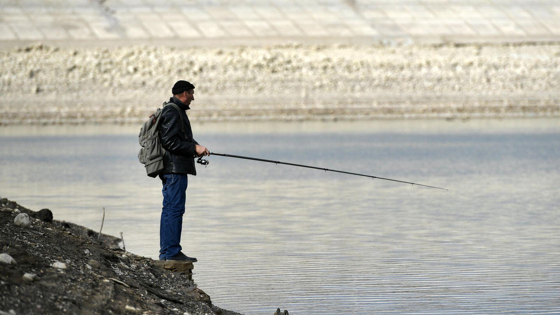 Человек ловит рыбу на берегу Аянского водохранилища в Крыму - РИА Новости, 1920, 25.12.2020