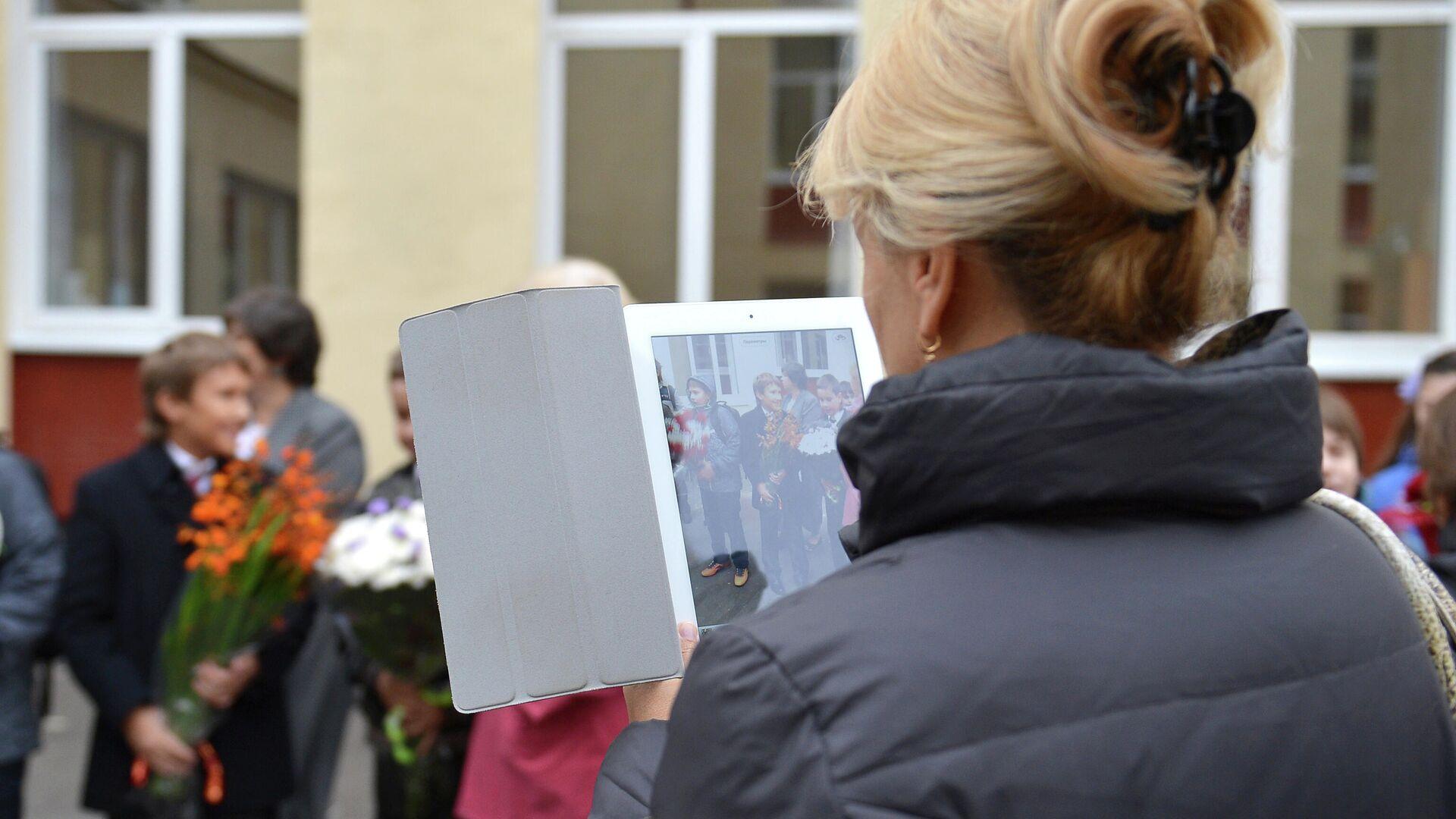 Женщина фотографирует учащихся средней общеобразовательной школы - РИА Новости, 1920, 17.03.2021