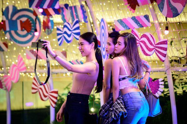 Девушки фотографируются возле торгового центра в Бангкоке