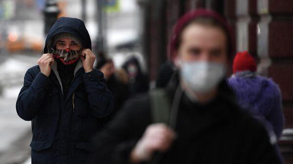 Прохожие в защитных масках на одной из улиц в Москве