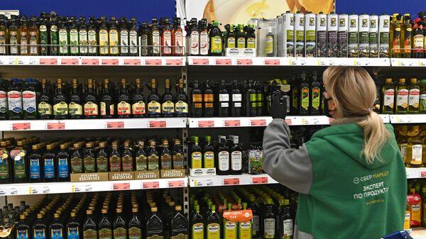 Продавец расставляет бутылки с растительным маслом на полке магазина