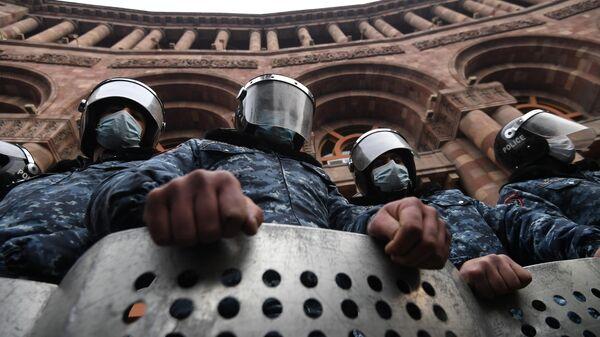Сотрудники полиции стоят в оцеплении перед зданием правительства Армении во время митинга оппозиции на площади Республики в Ереване