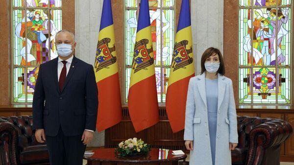 Бывший президент Молдавии Игорь Додон и избранный президент страны Майя Санду во время официальной передачи полномочий