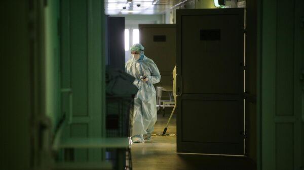 Медик в защитном противоэпидемическом костюме идет по коридору Новосибирской областной клинической больницы