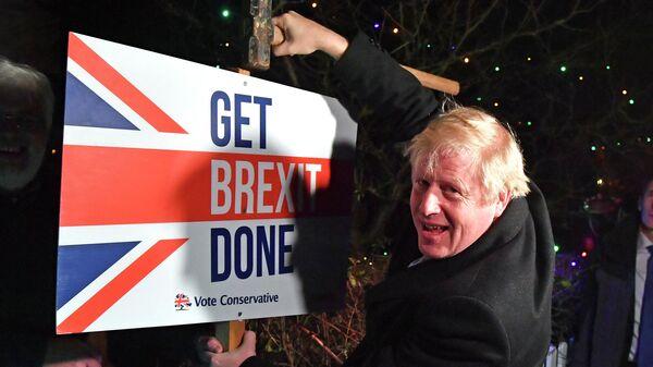 Премьер-министр Великобритании Борис Джонсон с табличкой Get Brexit Done
