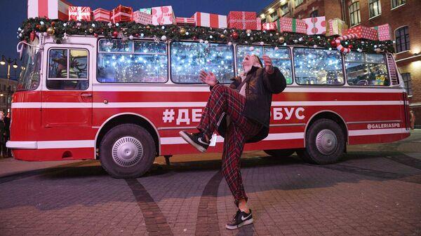 Прохожий на фоне праздничного Дедморобуса с музыкантами в костюмах Дедов Морозов, который ездит по улицам Санкт-Петербурга в преддверии нового года