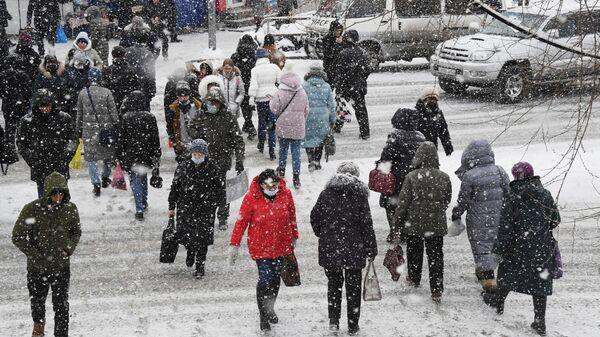 Прохожие во время снегопада во Владивостоке